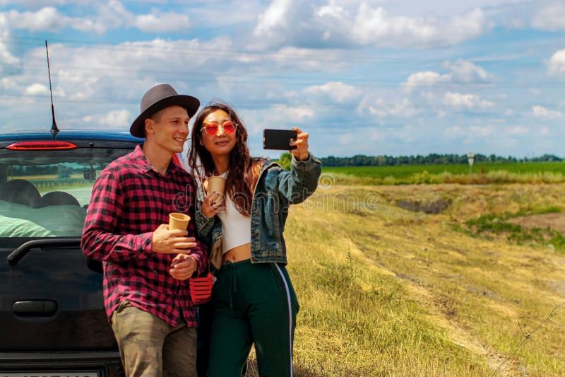 Concetto di viaggio, di amore, della data e della gente - coppia felice che abbraccia rilassamento sulla strada immagini stock libere da diritti