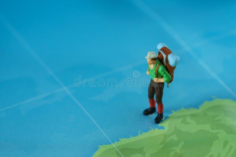 Concetto di viaggio come figura miniatura con lo zaino che cammina sul mA immagine stock