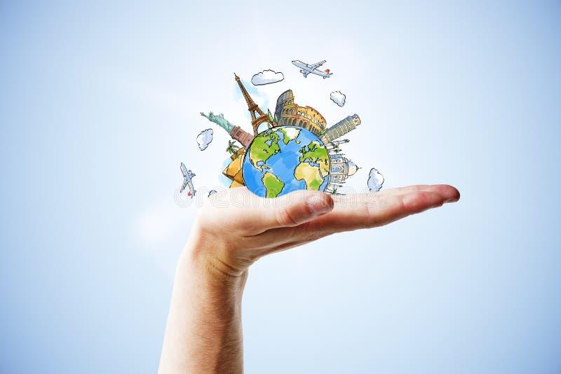 Concetto di viaggio con la mano ed il pianeta tirato della terra con i punti di riferimento immagini stock