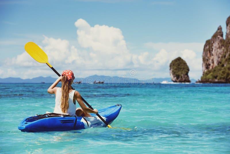 Concetto di viaggio con la singola ragazza sul kajak alla baia tropicale immagine stock libera da diritti