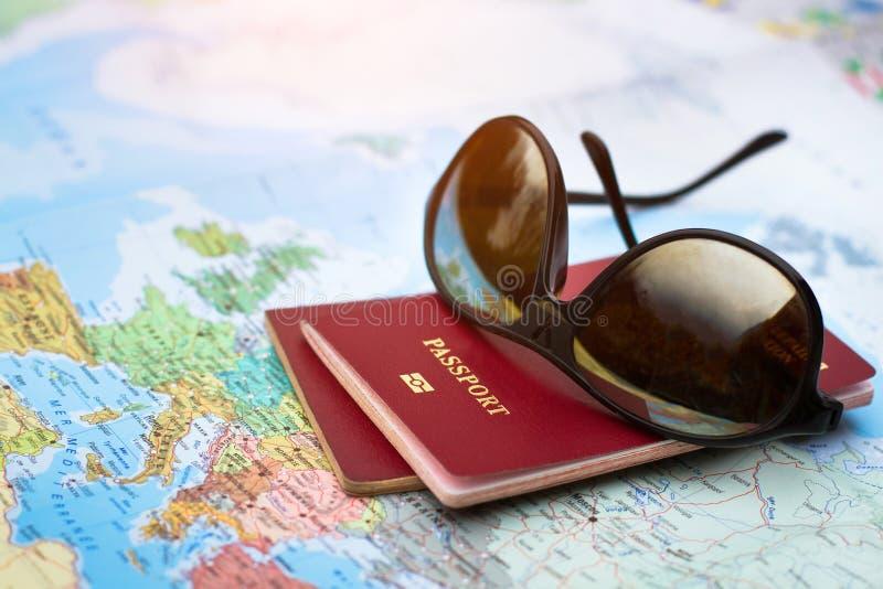Concetto di viaggio, due passaporti sulla mappa del mondo, feste immagini stock