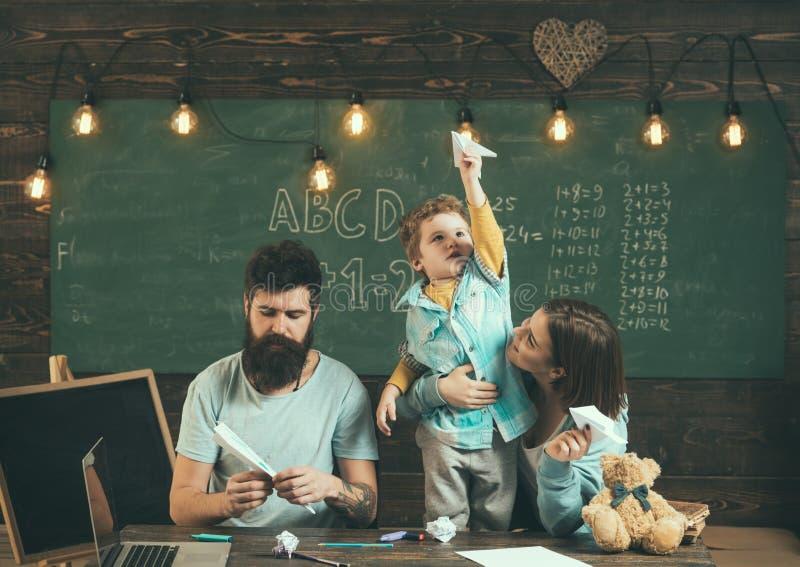 Concetto di viaggio La carta del lancio della famiglia spiana nella classe di scuola, viaggiante Viaggiando in aereo Il viaggio e fotografia stock