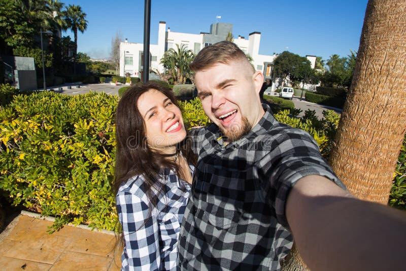 Concetto di viaggio, di vacanza e di festa - coppia divertente felice che prende selfie sulla via immagini stock libere da diritti