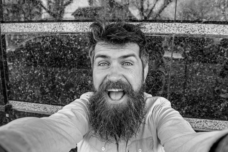 Concetto di Vlogging Uomo, turista con la barba e baffi sul fronte allegro e sorridente, fondo di marmo nero hipster fotografie stock libere da diritti