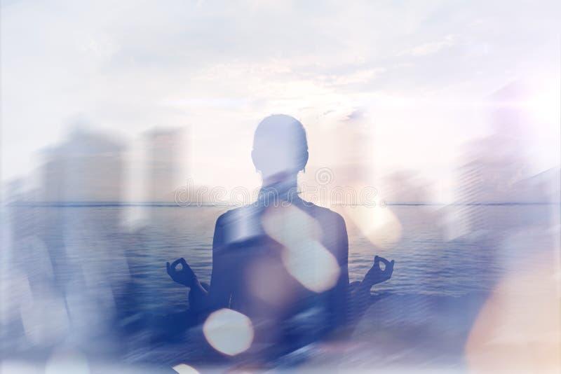 Concetto di yoga Doppia esposizione Donna che fa pratica di yoga sulla spiaggia e sulla siluetta della città moderna fotografie stock