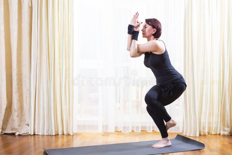 Concetto di yoga Esercizio di pratica di yoga della donna caucasica all'interno al pomeriggio luminoso Stando nella posa di Garud fotografia stock libera da diritti
