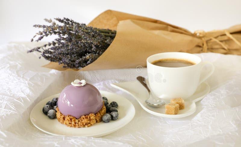 Concetto dolce di ora di colazione di mattina, bello dolce viola, mirtilli, tazza di caffè vicino al mazzo di lavanda sopra immagine stock libera da diritti