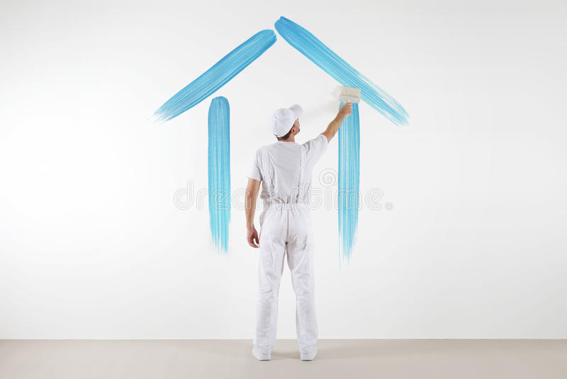 Concetto domestico di servizio uomo del pittore con il disegno di spazzola una casa blu fotografia stock libera da diritti