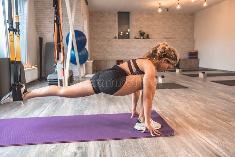 Concetto duro degli esercizi d'allungamento di un corpo facendo uso di una pratica di signora delle bande elastiche delle cinghie fotografie stock