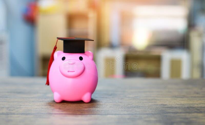 Concetto e borse di studio di istruzione con il cappuccio di graduazione in porcellino salvadanaio rosa sulla tavola di legno fotografie stock