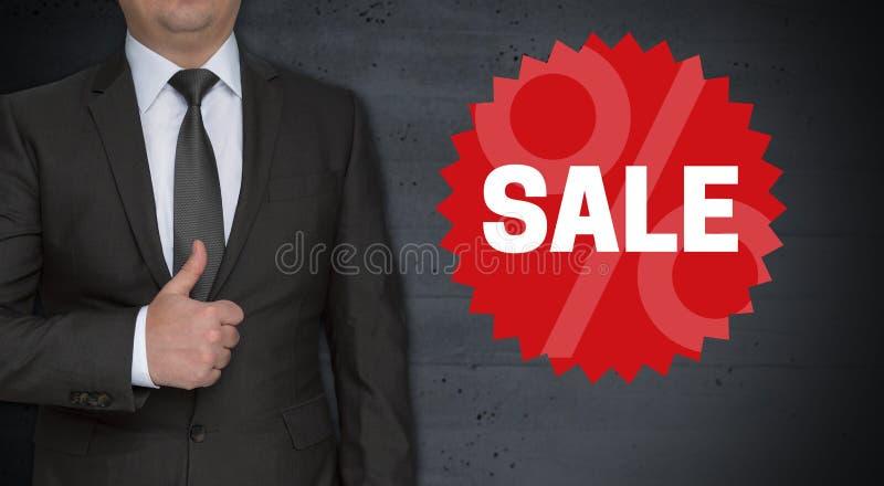 Concetto ed uomo d'affari del bollo di vendita con i pollici su fotografia stock libera da diritti