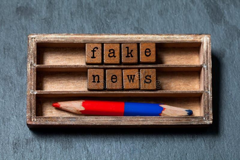 Concetto falso di notizie I cubi di legno della scatola d'annata esprime le parole false delle lettere di vecchio stile di notizi fotografia stock libera da diritti