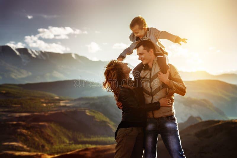 Concetto felice di divertimento della famiglia al tramonto fotografia stock