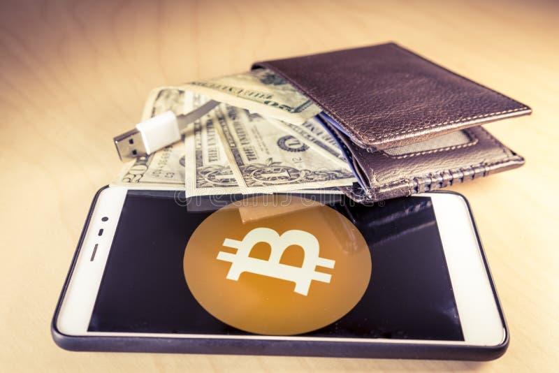 Concetto finanziario con un portafoglio con i dollari americani, il cavo di USB e lo smartphone con il logo del bitcoin fotografie stock