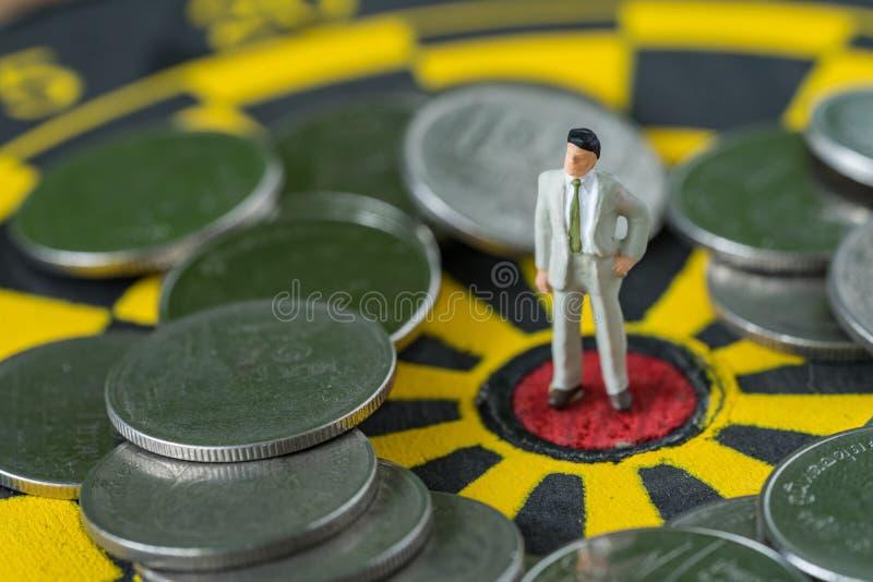 Concetto finanziario di affari come uomo miniatura di affari che sta a fotografia stock