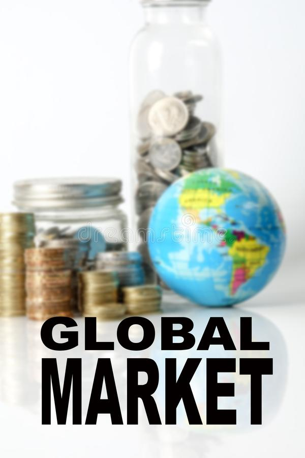 Concetto finanziario di economia globale con il globo della sfera, impilato delle monete e dell'iscrizione del MERCATO GLOBALE Im fotografia stock libera da diritti