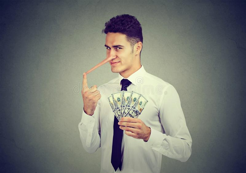 Concetto finanziario di frode Giovane uomo di affari del bugiardo sleale con i contanti del dollaro fotografia stock libera da diritti