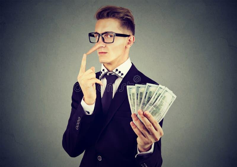 Concetto finanziario di frode Uomo di affari del bugiardo in vestito e vetri con i contanti del dollaro immagine stock