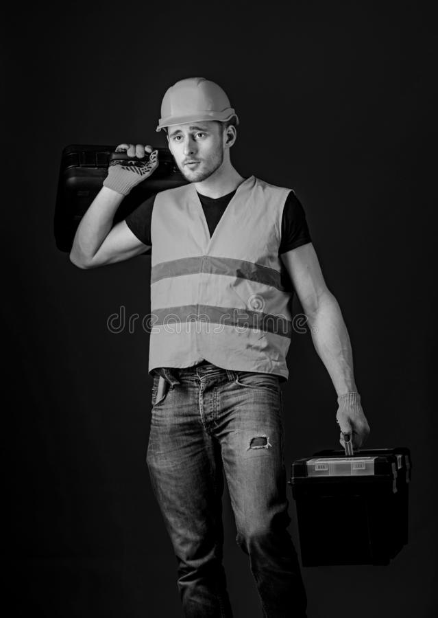 Concetto fornito del riparatore Il lavoratore, tuttofare, riparatore, costruttore sul fronte calmo porta la valigia con gli strum immagine stock