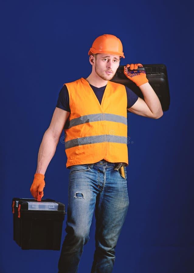 Concetto fornito del riparatore Il lavoratore, tuttofare, riparatore, costruttore sul fronte calmo porta la valigia con gli strum immagini stock