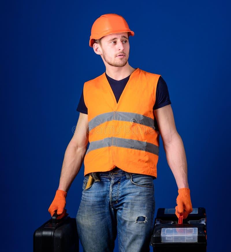 Concetto fornito del riparatore L'uomo in casco, casco tiene la cassetta portautensili e la valigia con gli strumenti, fondo blu  immagine stock libera da diritti