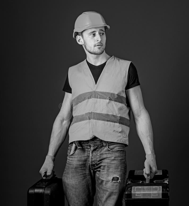 Concetto fornito del riparatore L'uomo in casco, casco tiene la cassetta portautensili e la valigia con gli strumenti, fondo blu  fotografia stock
