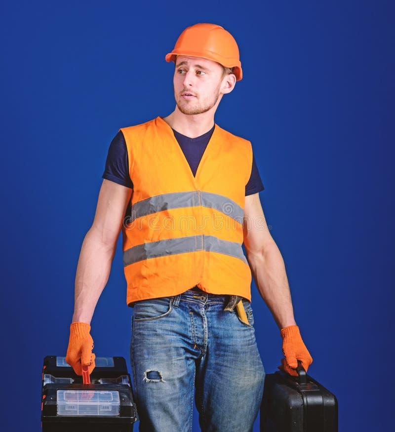 Concetto fornito del riparatore L'uomo in casco, casco tiene la cassetta portautensili e la valigia con gli strumenti, fondo blu  immagine stock