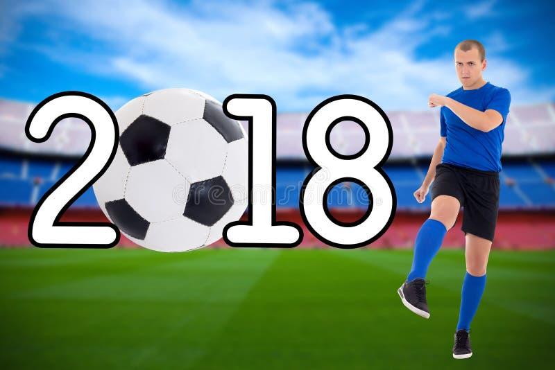 Concetto 2018 - giovane calciatore di calcio che dà dei calci alla palla sul fotografia stock