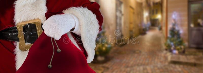 Concetto il Babbo Natale di Natale che sta sulle vie di piccolo vicolo che giudica il suo borsa pieno dei presente immagini stock libere da diritti