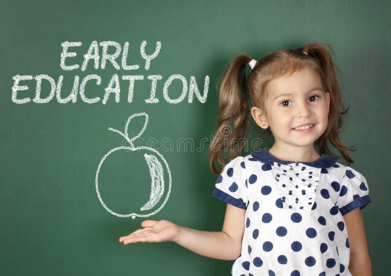 Concetto iniziale di istruzione, ragazza del bambino vicino alla lavagna della scuola fotografia stock