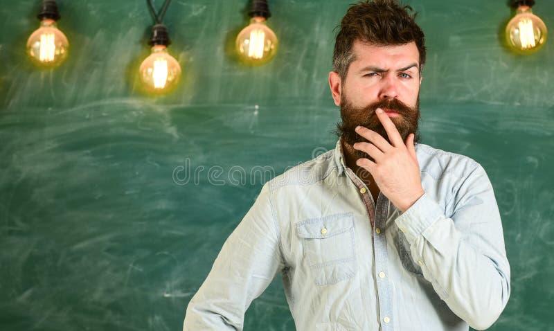 Concetto intellettuale di compito Pantaloni a vita bassa barbuti in camicia, lavagna su fondo Uomo con la barba e baffi su premur fotografie stock