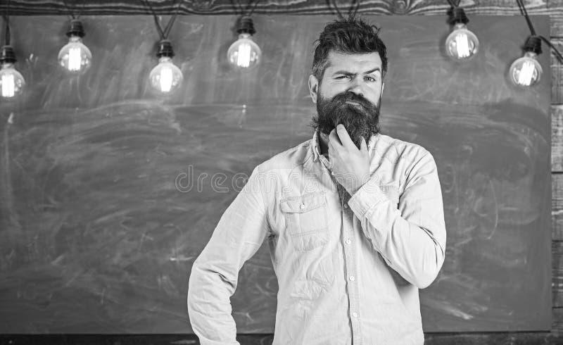 Concetto intellettuale di compito Pantaloni a vita bassa barbuti in camicia, lavagna su fondo Uomo con la barba e baffi su premur fotografia stock libera da diritti