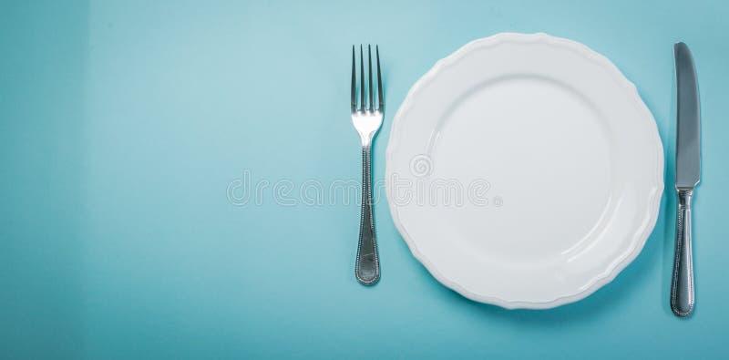 Concetto intermittente di fastin - piatto vuoto su fondo blu immagini stock