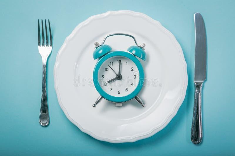 Concetto intermittente di fastin - piatto vuoto su fondo blu fotografia stock libera da diritti