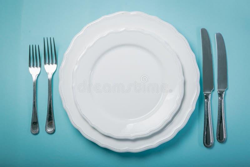 Concetto intermittente di fastin - piatto vuoto su fondo blu fotografia stock