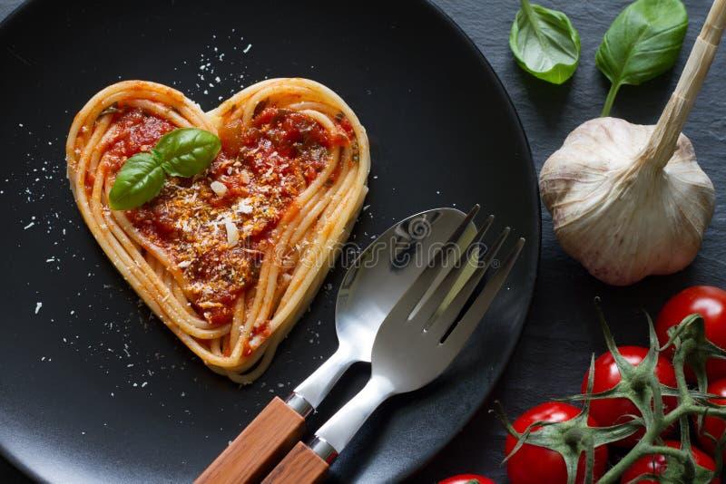 Concetto italiano dell'estratto di dieta di alimento di amore del cuore della pasta degli spaghetti su fondo nero fotografia stock libera da diritti