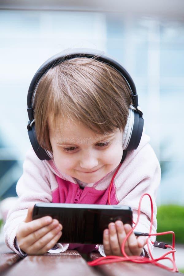 Concetto: L'apprendimento è dappertutto ed in qualunque momento Ragazza del piccolo bambino che per mezzo del telefono cellulare  immagini stock
