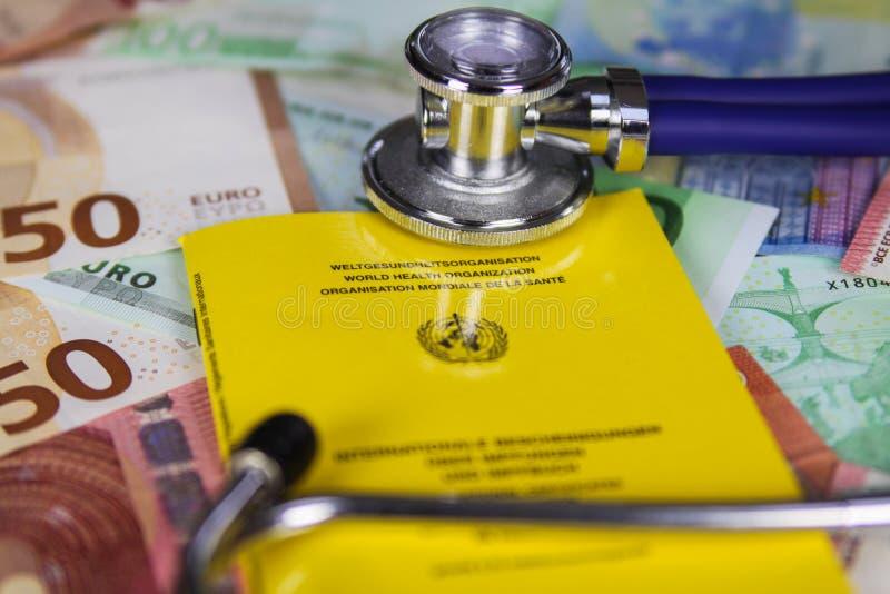 Concetto medico di costo di vaccinazione - stetoscopio e certificato di vaccinazione internazionale giallo sulle euro banconote d fotografie stock libere da diritti