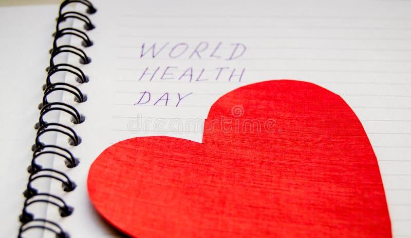 Concetto medico di sanità, fuoco selettivo su cuore rosso, scritto il giorno di salute di mondo del blocco note fotografia stock libera da diritti