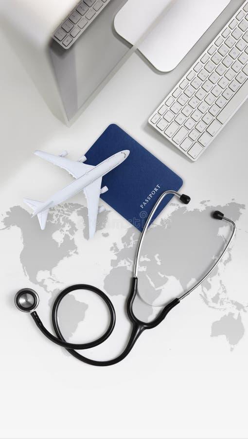 Concetto medico internazionale, stetoscopio, passaporto, computer ed aeroplano di assicurazione di viaggio nell'ufficio dello scr immagini stock