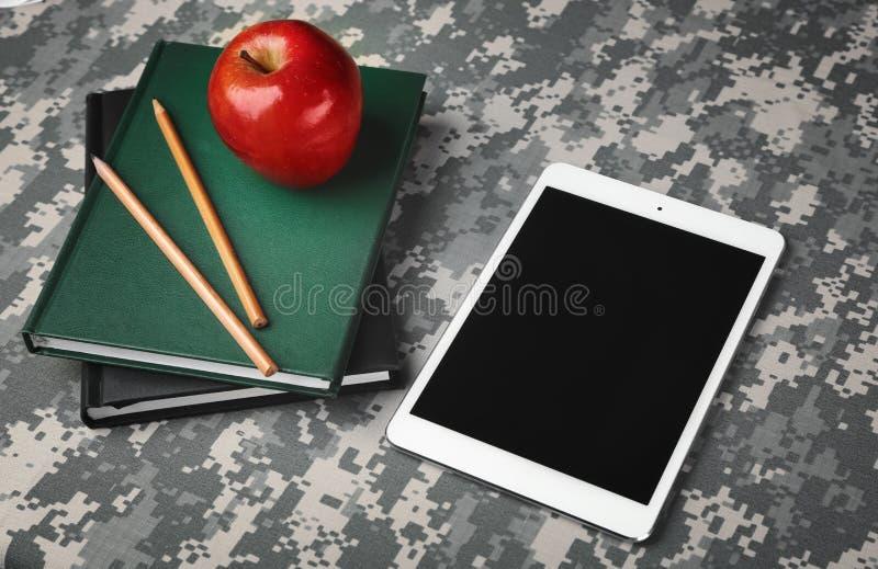 Concetto militare di istruzione Compressa, libri, matite e mela immagine stock