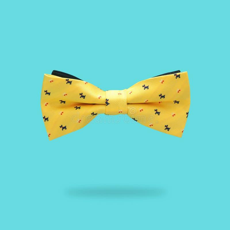 Concetto minimo cravatta a farfalla maschio gialla sopra fondo variopinto fotografia stock