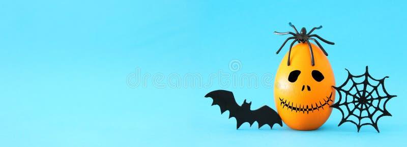 concetto minimo e divertente di festa di Halloween Uovo arancio con il fronte, la ragnatela, il pipistrello ed il ragno svegli sp fotografia stock libera da diritti