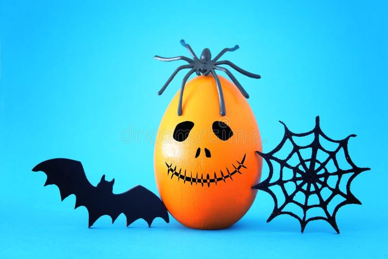 concetto minimo e divertente di festa di Halloween Uovo arancio con il fronte, la ragnatela, il pipistrello ed il ragno svegli sp fotografie stock