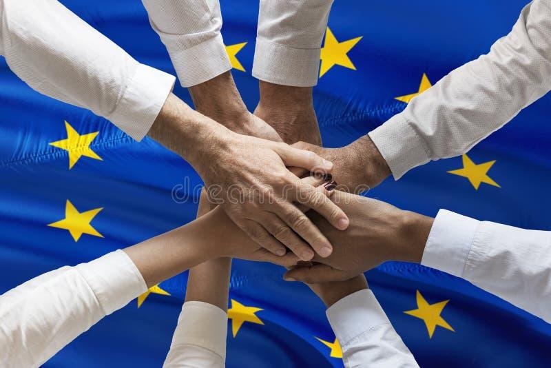 Concetto multiculturale del sindacato delle mani sopra la bandiera europea fotografia stock