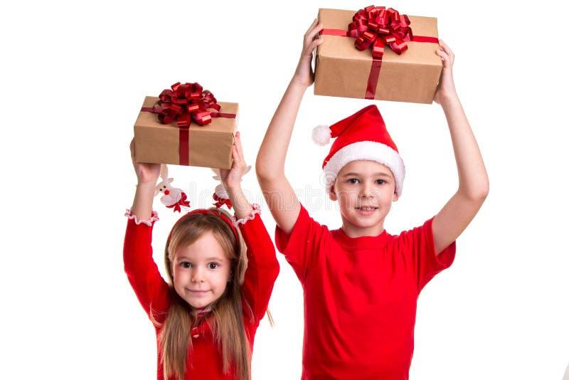 Concetto: natale o festa del buon anno Ragazzo allegro con il cappello di Santa sulla sua testa e su una ragazza con i corni dei  immagini stock
