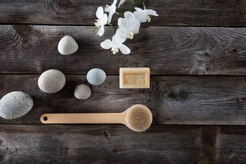 Concetto naturale del bagno con i ciottoli, la spazzola della parte posteriore e le orchidee bianche immagini stock