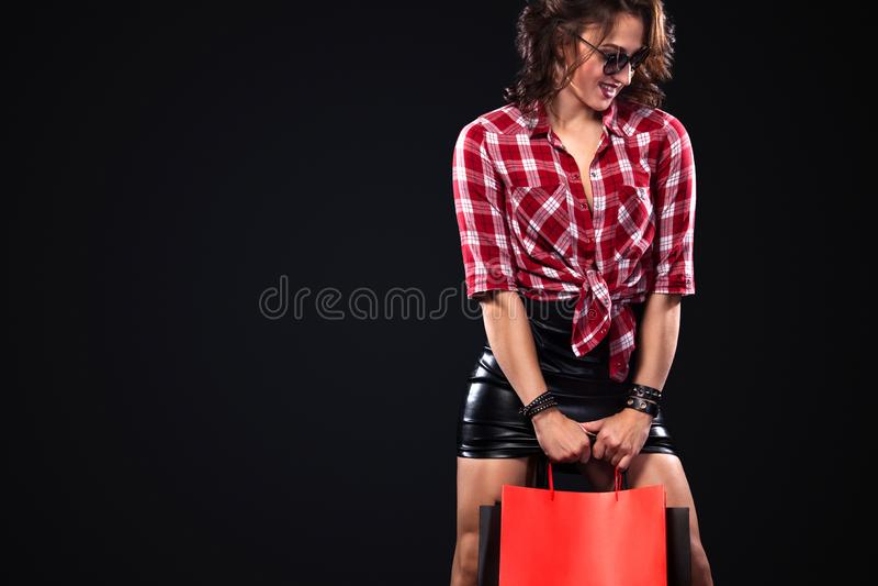 Concetto nero di vendita di venerdì Donna di acquisto che giudica le borse isolate su fondo scuro nella festa fotografie stock libere da diritti
