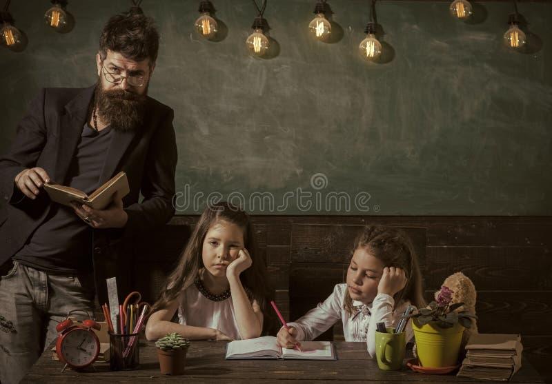 Concetto noioso di lezione Allievi delle ragazze e dell'insegnante in aula, lavagna su fondo L'uomo con la barba insegna a fotografie stock libere da diritti