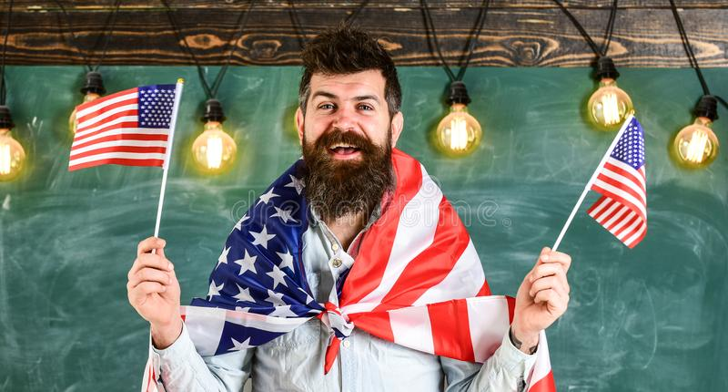 Concetto patriottico di istruzione Programma di scambio dello studente L'uomo con la barba ed i baffi sul fronte felice tiene le  immagine stock libera da diritti